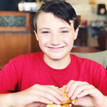 Conner with a bacon and egg bagel at Einstein Bros.